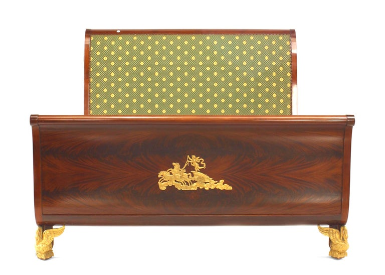 French Empire style sleigh form queen sized bed. The bed rests upon gilt bronze eagle feet and features figural applied gilt bronze accents and a headboard upholstered in green polka dot fabric.