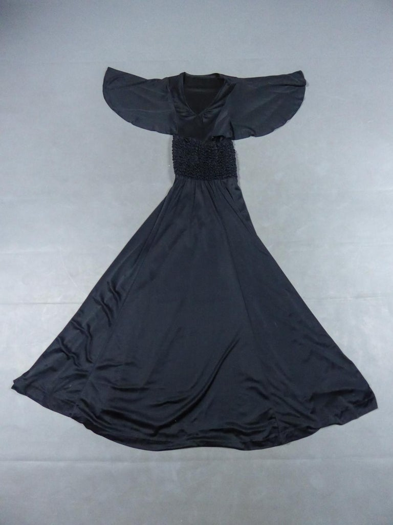Circa 1990 France  Long evening dress inblack strech silk jerseyfrom the 90s. Skin-tight cutat the level of the bustier flaring from the waist leaving a fluid and loose skirt. Gathered neckline in V-shape, bat sleeves and waist marked by a