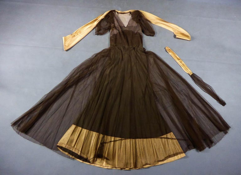 Circa 1930/1940 France  Elegant long evening dress, collector's item, in cotton tulle and gold goffered satin with skin effect dating from the 1930s. Interesting structure with transparency effect: built-in under-dress in brown silk crepe with
