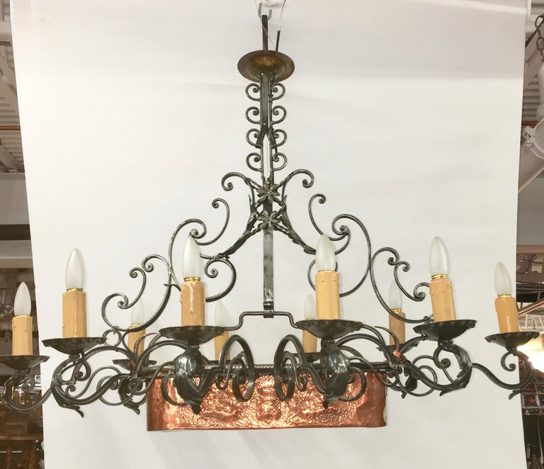 Beautifully handcrafted wrought iron chandelier on a linear rectangular axis having ten lights around a fixed central planter of hand hammered copper with repousse designs of flowers on one side and the crest and shield of a noble family on the