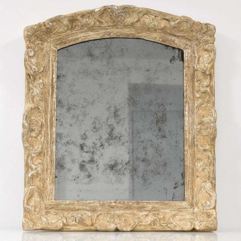 Museum-quality elegant 17th Century hand-carved oak wall mirror. High-quality Louis XIV period framing with silver leaf gilding in 'a la Berain' carved design. The silver leaf has worn through to expose the reddish-brown 'bole' or gilder's clay.