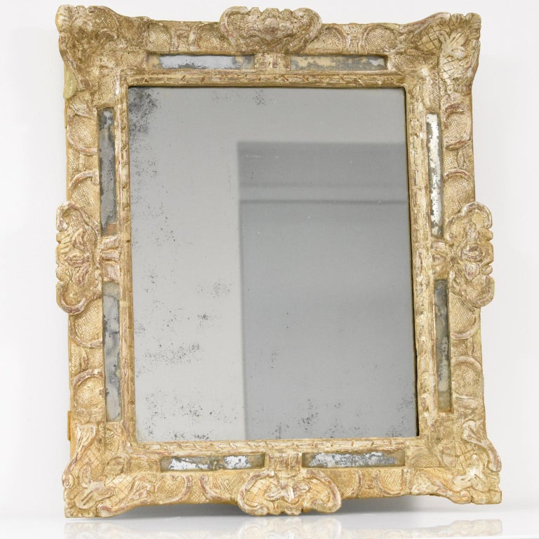 Elegant 17th Century hand-carved oak wall mirror. High-quality Louis XIV period framing with silver leaf gilding in 'a la Berain' carved design compliment with parclose mirrors. The silver leaf has worn through to expose the reddish-brown 'bole' or