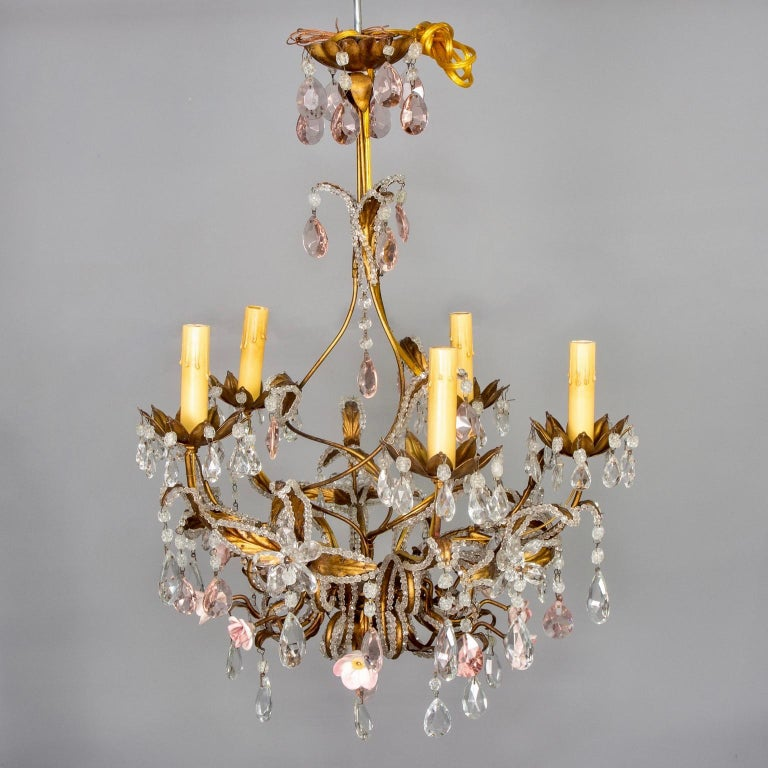 Five-light French gilt metal chandelier is embellished with clear and pink crystal drops, clear crystal flowers, extensive crystal beading and pale pink porcelain roses, circa 1930s. New wiring for US electrical standards. Candelabra sized sockets.