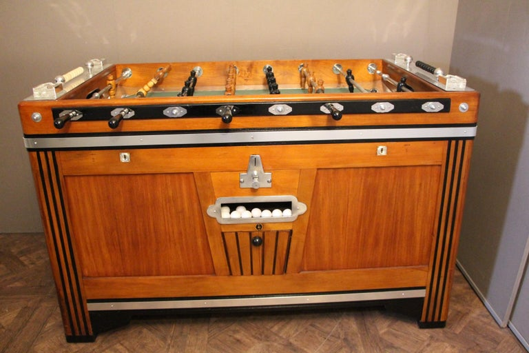 Unusual shape of French foosball table, this item is spectacular. It is in light color wood and blackened wood and features many aluminum pieces. Nice job of inlay on its sides. Its players are in black and honey color carved wood. Green field and