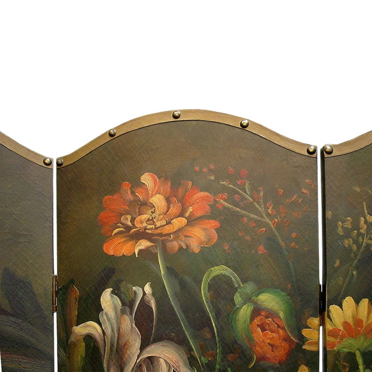 A very decorative French four-panel painted screen. The four painted panels are bordered by antique nails over brown leather trim. The whole is hand painted showing a large urn on top of a table with a very stunning bouquet of colorful flowers