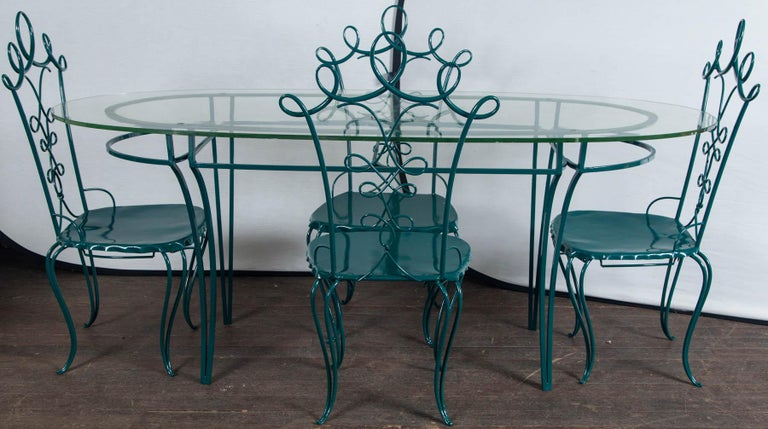 1940s French wrought iron garden table with and oval half inch thick glass top, four wrought iron looped chairs after René Prou. Four drilled holes on top line up with holes on iron base. Newly professionally refinished in a green color. Measures: