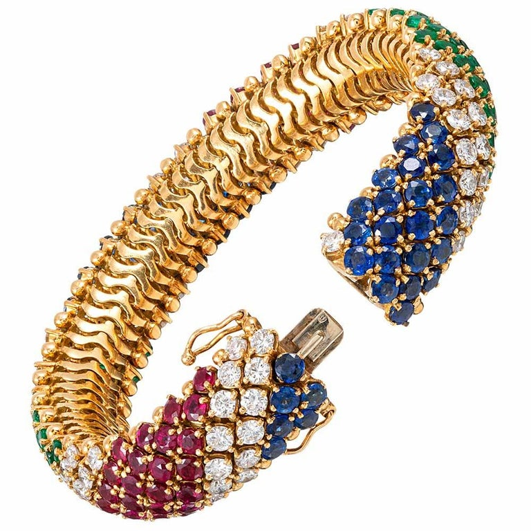 Exquisitely appointed with royal blue sapphires (11.20 carats), rich red rubies (8.50 carats), intense green emeralds (6.16 carats) and brilliant white diamonds (8.40 carats), this striking bracelet marries classic design often seen in the creations