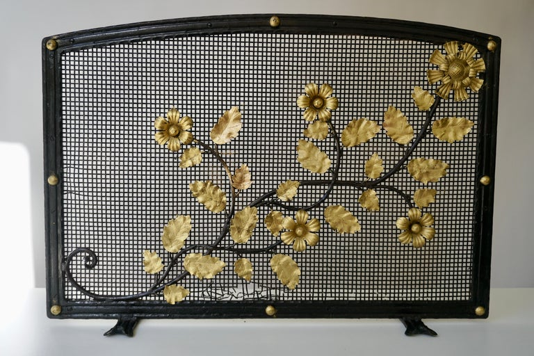 Fire screen with scattered golden flowers mounted on black metal rods. Mesh backing makes these an excellent choice for wood-burning fireplaces.  Custom inquiries welcome.  Weight 7kg.