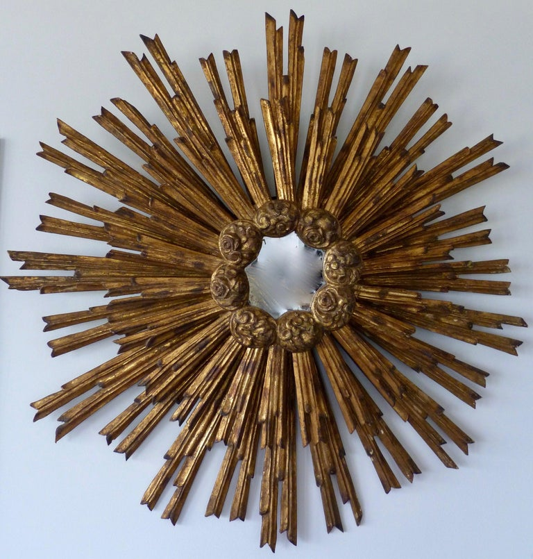 A French gilded sunburst mirror, second half of the 19th century.  Made of 2 overlapping Sunburst parts joined together with carved flower buds around the middle rim.