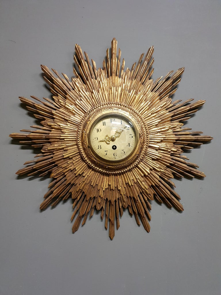 A mindblowing radiant sunburst clock by the French clockmaker Japy Frères, circa 1920. This impressive and functional wall sculpture is made out of gilded carved wood. A true piece of art. The clock is engraved with the Japy Frères brand and
