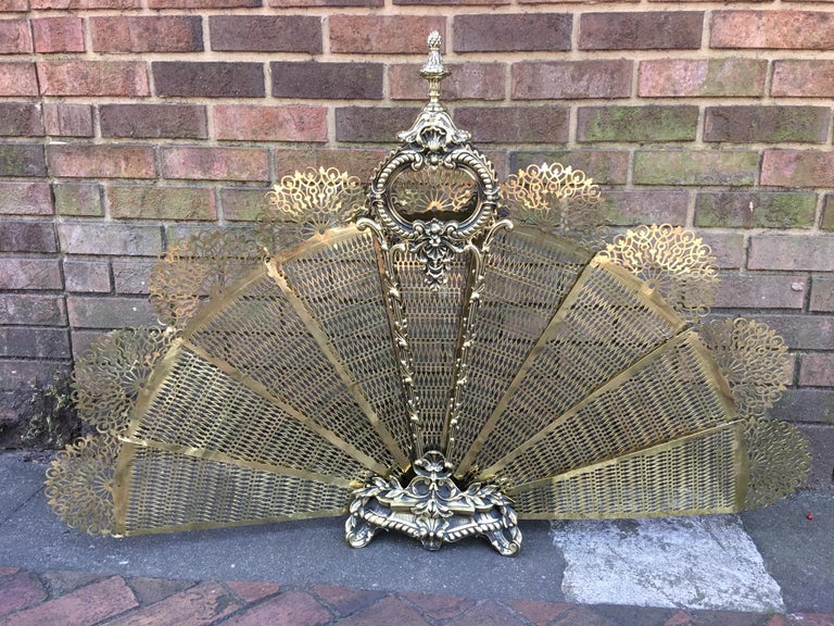 French gilt brass decorative pierced folding fire place fan screen with a decorative, intertwined scrolled floral swags with a round medallion, centered supporting bead work, and resting on a step back foliage and floral medallion, and fluted finial