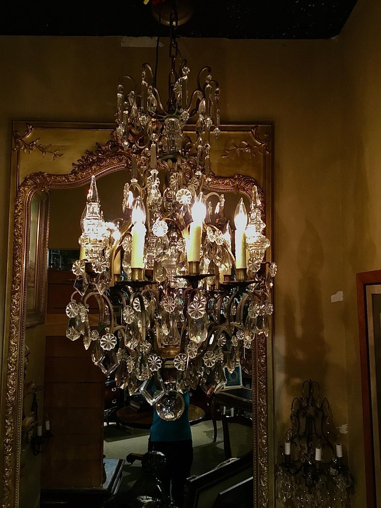 Three finiaks and nine-light on the perimeter and a finial in the center, Having clear and lavender crystals. Scrolling arms and bronze flora form Candle cups. The top two tiers hung with spires and clear crystal drops.