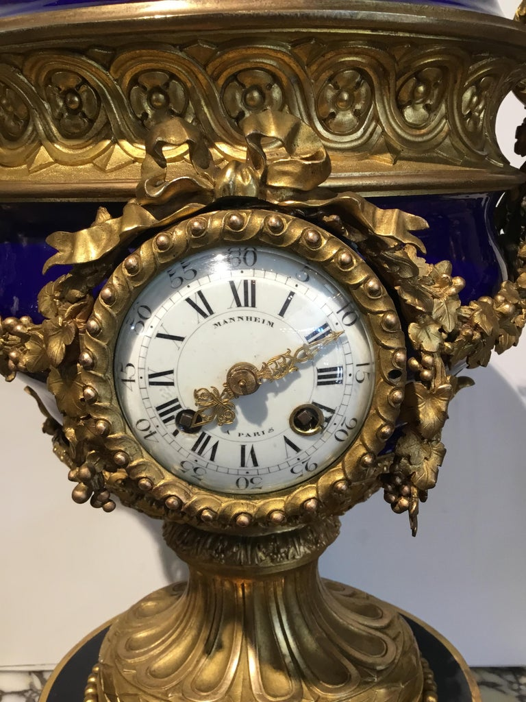 Large and exquisite urn form clock with cobalt porcelain and gilt bronze Mounts. Signed on face Mannheim Paris. Pomegranate finial at the crest. Scrolling arms to each side in grape leaf motif. Urn is resting on a circular Base on gilt bronze.