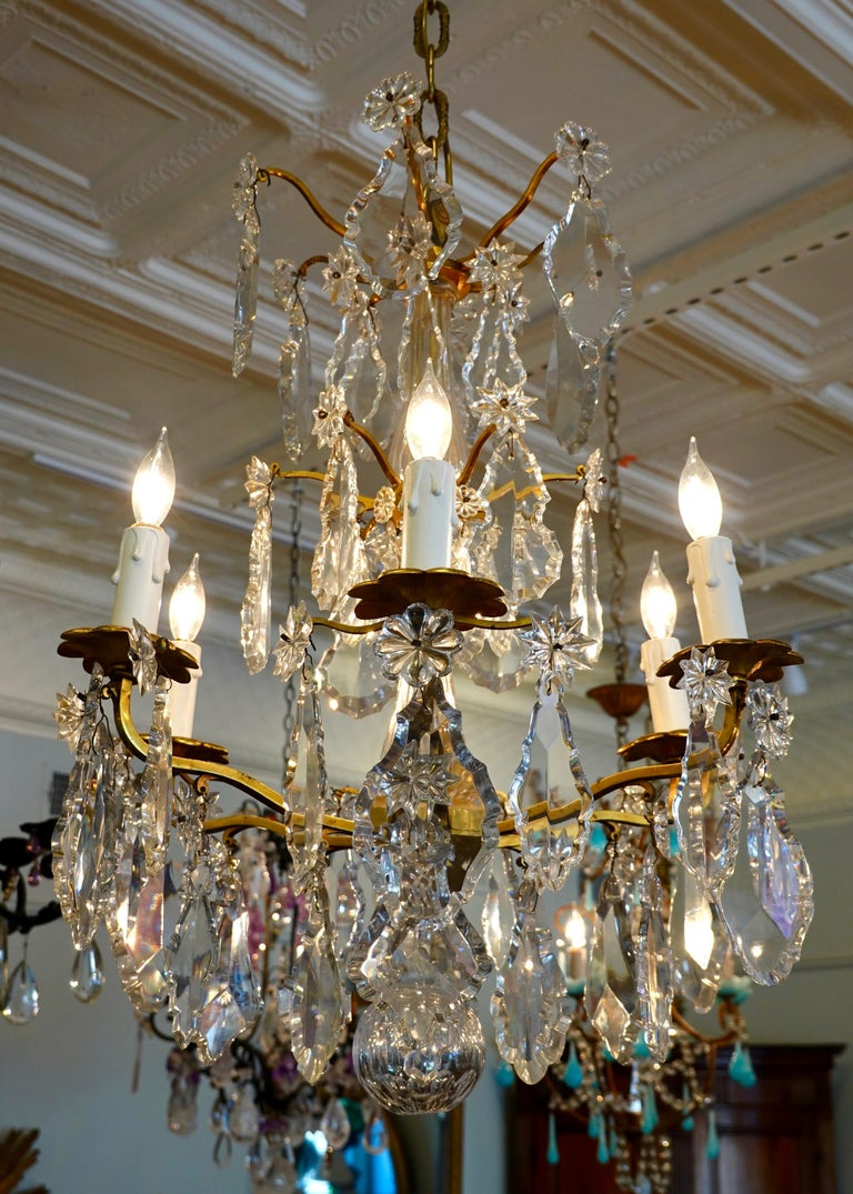 French Louis XV style gilt-bronze and crystal chandelier, electrified with six lights. This chandelier features exceptional, large cut crystal pendalogues, stars and rosettes, and a hollow cut crystal ball. The chandelier has been rewired for the US.
