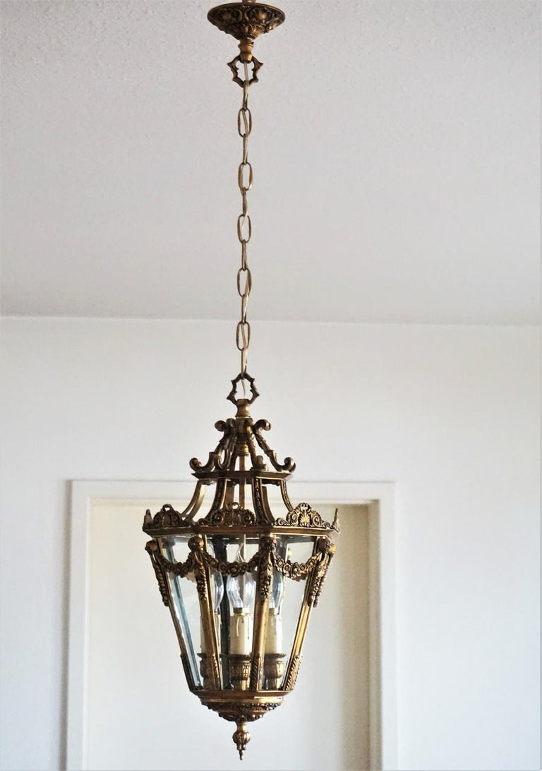 French gilt bronze lantern with four-bulb candelabra cluster surrounded by eight clear glass panels. The lantern is beautifully ornate with floral swags and ornaments, late 19th century. Great aged patina to bronze. Four E14 light bulb sockets with