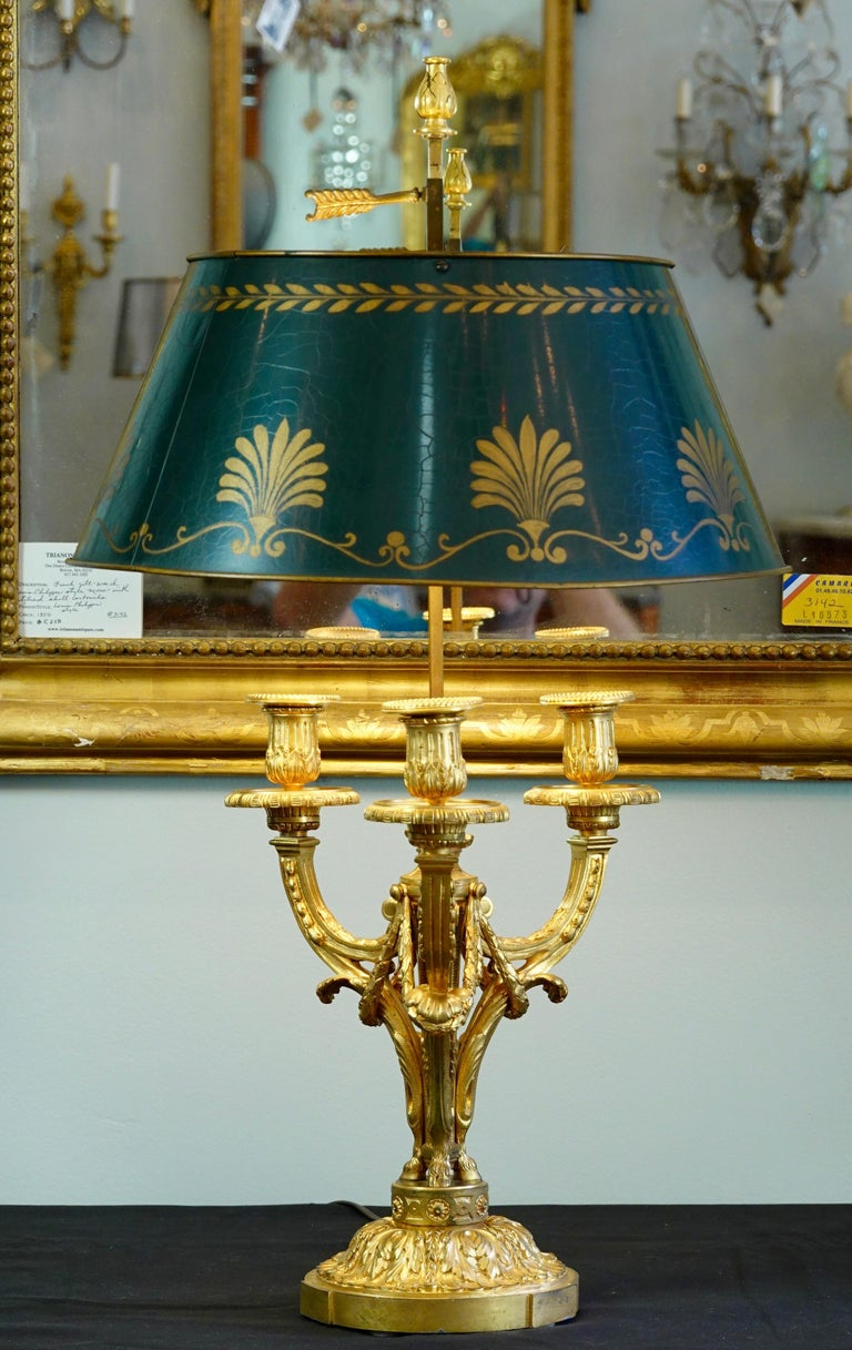 Very nice quality, French, Louis XVI style gilt bronze Bouillotte lamp with green painted tole shade, (19th century). The lamp features nicely chiseled acanthus leaves, garlands, central flame, hoofed feet and other neoclassical details. The painted