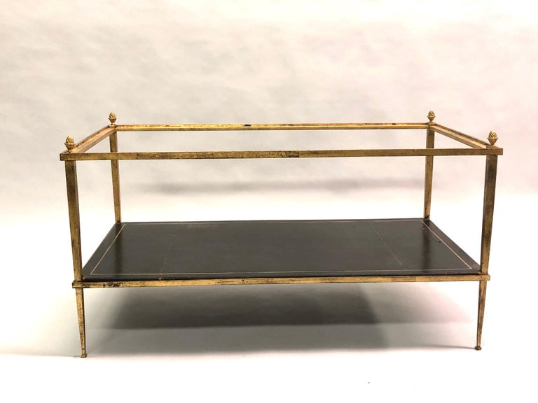 French double level modern neoclassical coffee table manufactured by Maison Ramsay for Maison Jansen in gilt iron with delicate line and tapered legs. The table features a gold embossed leather lower level, a clear glass upper level and is finished