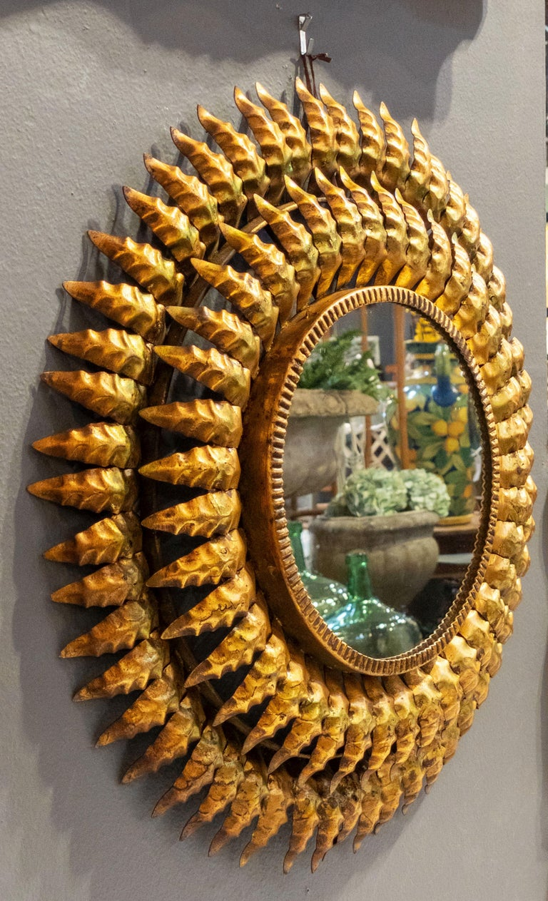 A lovely French sunburst (or starburst) mirror of gilt metal, 20 inches diameter, with round mirrored glass center in moulded frame.