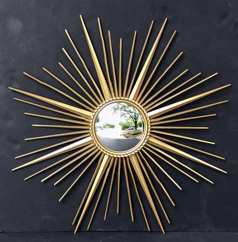 A fine French gilt metal sunburst (or starburst) mirror, 33 3/4 inches diameter, with convex mirrored glass center in moulded frame with rope motif trim by Chaty Vallauris.  With impressed mark of maker on back.  The Chaty Vallauris starburst or