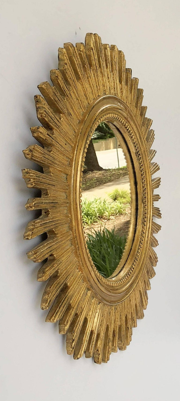 A lovely French gilt sunburst (or starburst) mirror, 20 1/2 inches diameter, with round mirrored glass centre in moulded frame.