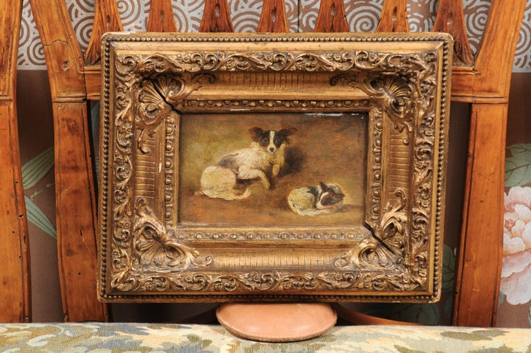 A giltwood framed oil on panel painting of 2 papillon dogs. The painting dating from the late 19th century and French and origin.