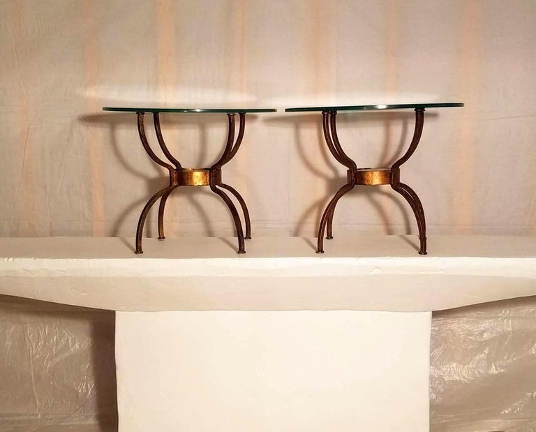 A pair of French wrought iron gilt end tables.  The spider leg frames radiate out from thick cast amber glass discs 14 cm. x 2.5 cm. thick. The tables are in good condition.