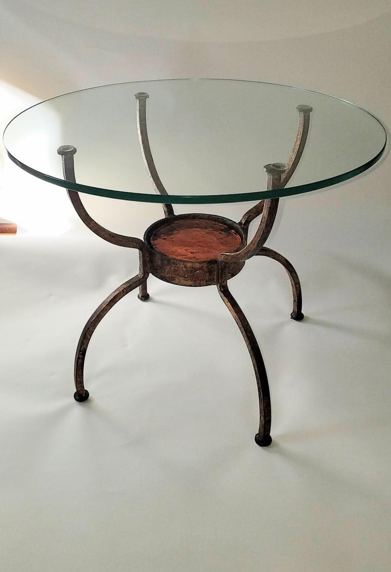 French wrought iron gilt end table.  The spider leg frame holds a cast amber glass disc 14 cm. x 2.5 cm. thick. The table is in good condition.