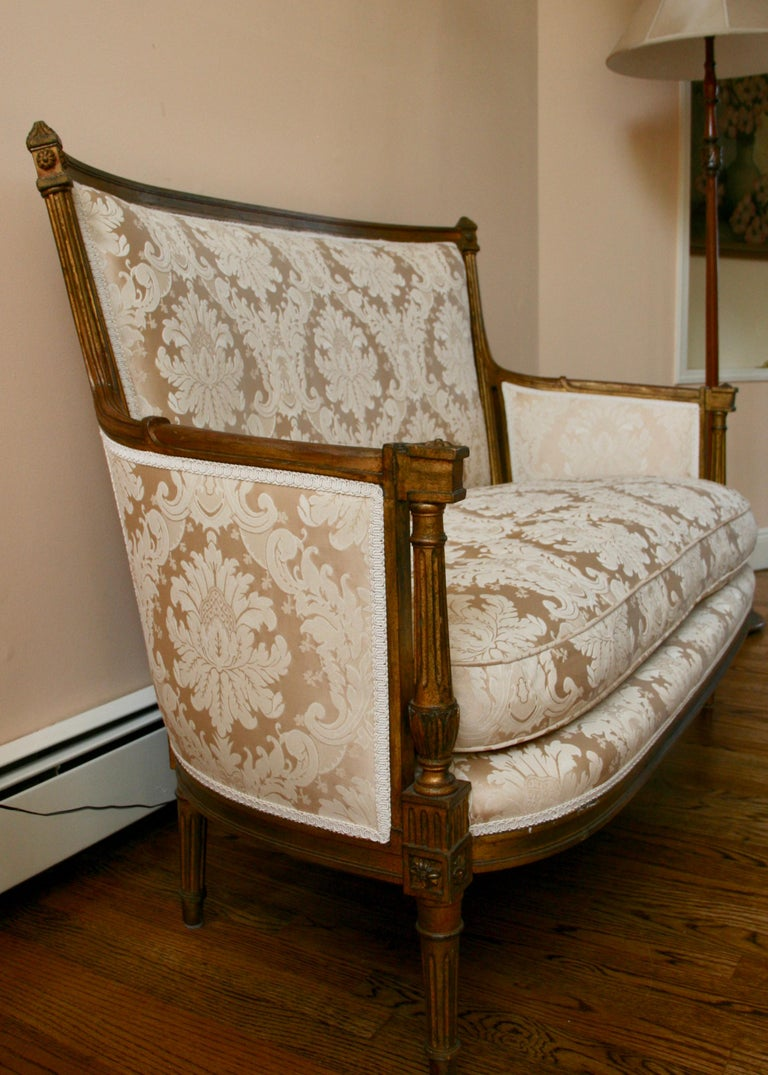 A French Louis XVI style giltwood sofa settee with white new damask upholstery. Structurally sound in good original conditions.
