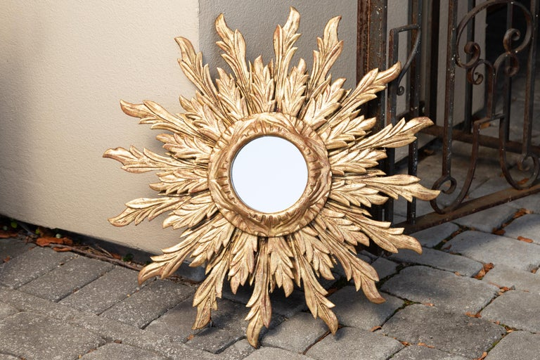 A French giltwood double layered sunburst mirror from the mid-20th century, with wavy sunrays. Born in France during the midcentury period, this exquisite vintage piece features a small size round mirror plate framed by a carved giltwood molding. On
