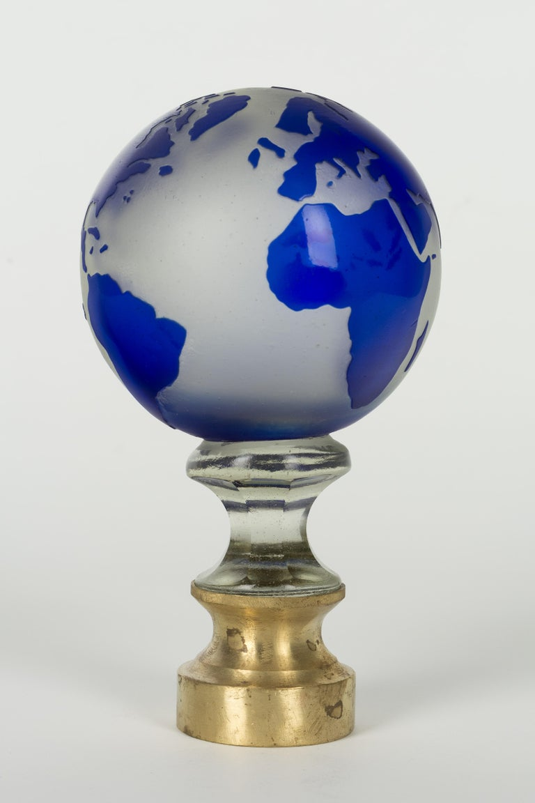 An early 20th century French glass globe newel post finial or boule d'escalier. These wonderful finials were used as decorative elements at the bottom of a staircase on the newel post. This one is made of two layers of cased glass with the cobalt
