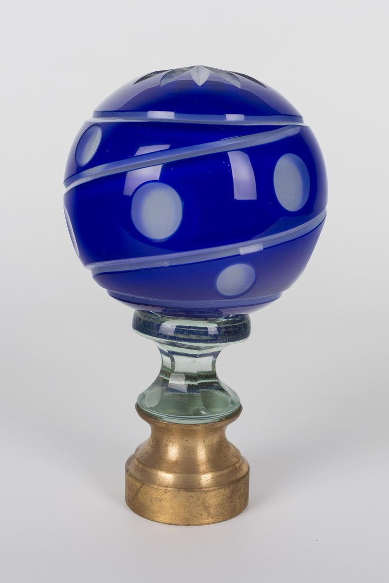 An early 20th century French glass newel post finial or boule d'escalier. These wonderful finials were used as decorative elements at the bottom of a staircase on the newel post. This one is made of two layers of cased glass with the cobalt glass