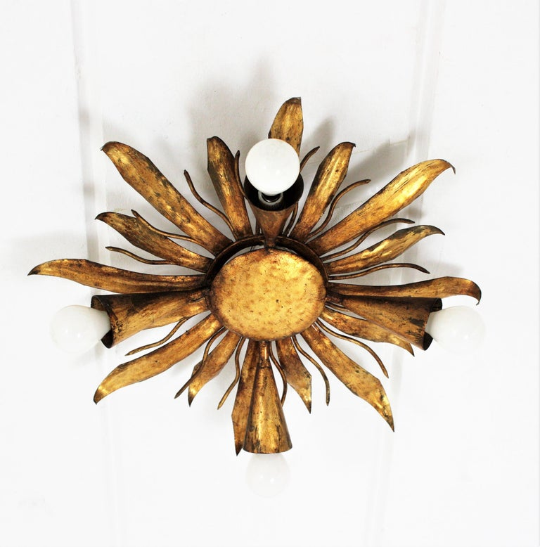 French modern neoclassical gilt iron leafed sunburst flush mount or light fixture from the late Art Deco period, France, 1940s. This sunburst or flower burst light fixture is highly decorative due to its design with alternating iron leaves with