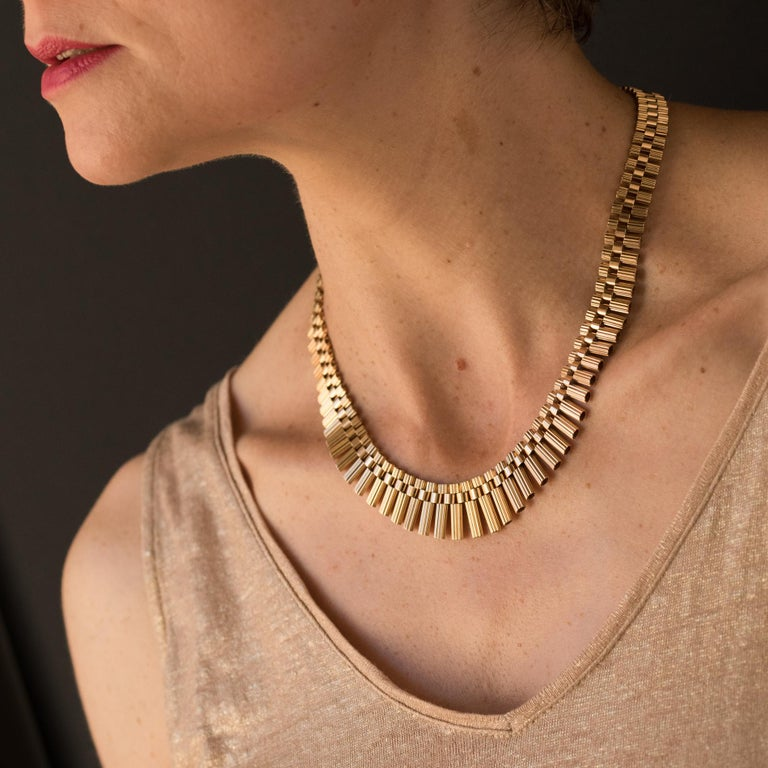 18K gold necklace, french eagle hallmark. This vintage gold necklace is formed by a cascade of flat chased hollow gold tubes that are linked with gold rings. This golden necklace is completed with an 8 ratchet security clasp.    Length: 44 cm, width