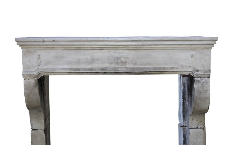 This country fireplace mantel (fireplace) is quite large and high. It is a Louis XIII fireplace in limestone with graffiti remains on the front and remains of the original patina. The remains of the old original paint can be more
