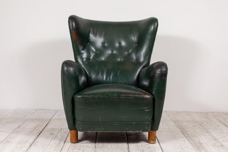 Elegant French green leather wingback chair with button details. The chair has been fully restored and it in excellent vintage condition. Legs are original which adds to the one of a kind character.