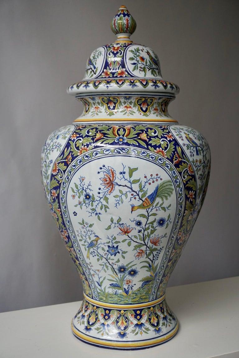 This elegant vase was crafted in Normandy, circa 1950. The ceramic, rounded potiche features hand painted flower decor with birds in a traditional blue, white, green and yellow palette. The lid of the porcelain vase is topped with three small bird