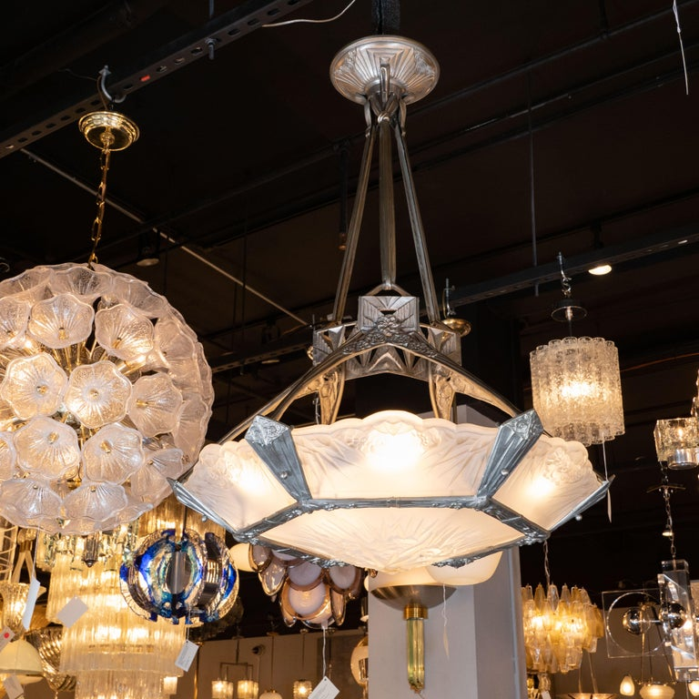 This elegant and sophisticated High style Art Deco Chandelier was realized in France, circa 1930. It features a hexagonal silvered bronze frame with stylized cubist geometric designs, including sunburst and cloud motifs. The frame supports six side