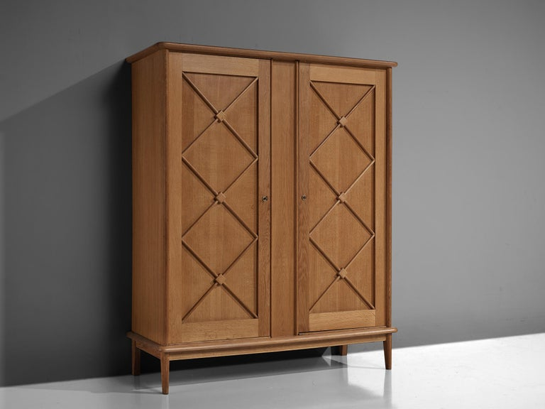 Cabinet, oak, France, 1960s  An elegant case piece in oak that features geometric details in the doors. The high board is lifted from the ground by slim, conical legs that give the solid looking body a more airy appearance. The cabinet offers