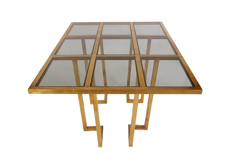 A gorgeous midcentury brass dining table from France, circa 1960s. It features a grid design with patinated brass and inlayed glass. Nice warm overall patina. Ready for use.