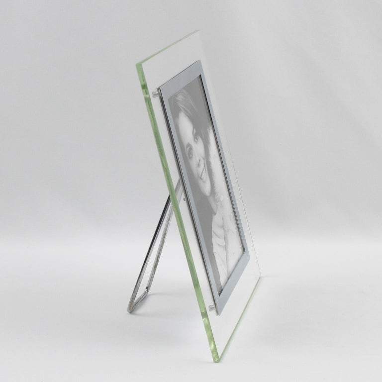 Lovely French Hollywood Regency glass picture photo frame. Elegant clear glass slab with geometric design and refined chromed metal framing all around the picture view. Metal easel at the back. Measurements: Overall: 7.88 in. wide (20 cm) x 9.88
