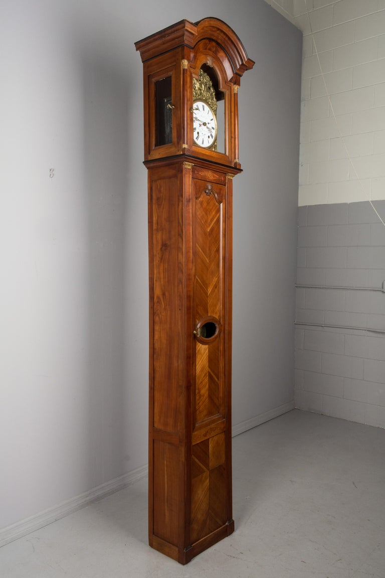 A 19th century French Horloge de Parquet or tall case clock from Brittany. Elegant solid cherry case in two parts, with book matched panels and a chapeau de gendarme crown. Subtle details including marquetry inlay and carved shell motif. Embossed