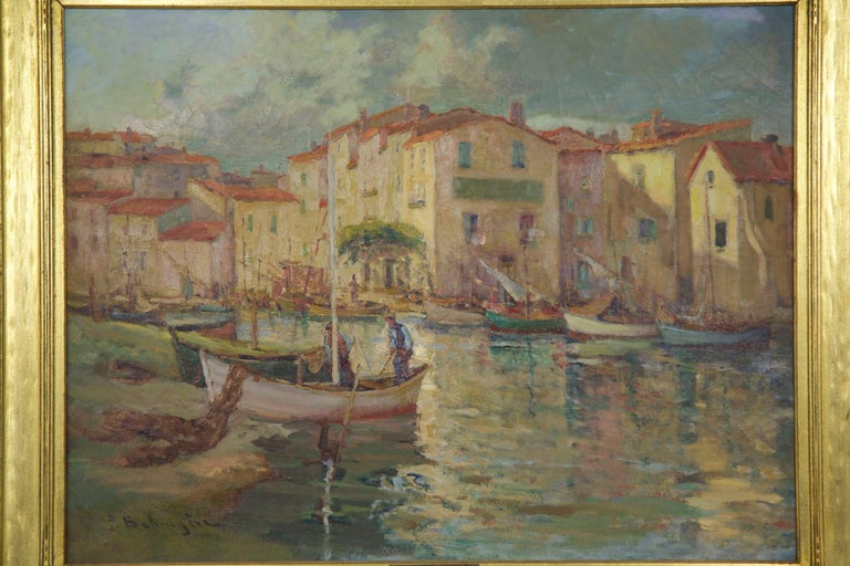 A beautiful coastal scene of a weathered harbor village with its colorful red clay roofs reflecting against the gentle blue waters, a fisherman prepares his boat for the next day while other boats are tied up along unseen docks. It is such a