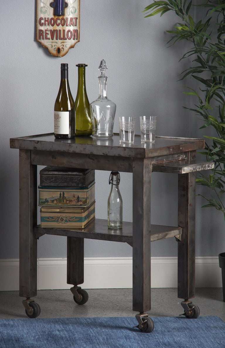 A vintage polished steel industrial working table, French, circa 1950. Rectangular form with square corner legs atop rolling casters, two with working brakes. The top has a thin, raised lip on three sides, with one short end open. The open end has a