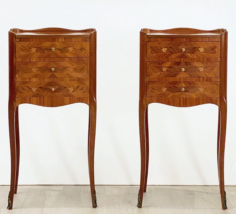 A fine pair of French bedside end tables or nightstands, each stand featuring an inlaid top with serpentine gallery over a frieze.