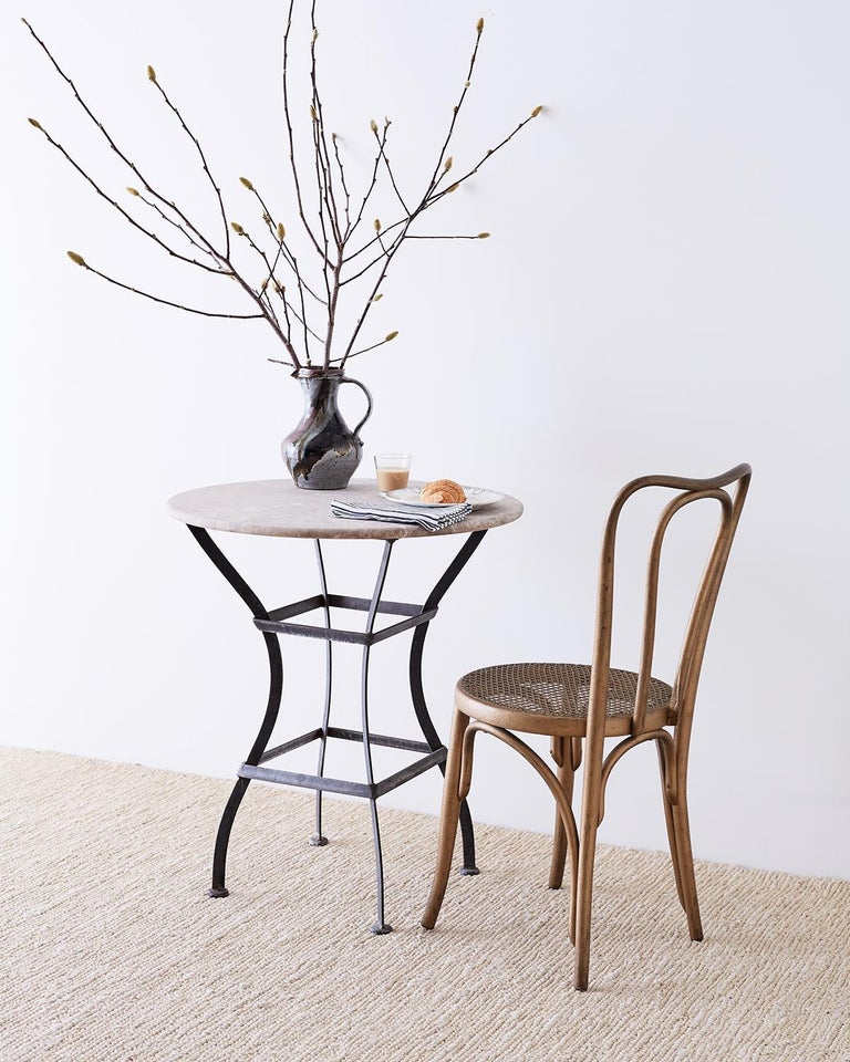 Sculptural French bistro table or cafe table featuring an iron base topped with a later molded stone top. The base is constructed from iron with an hourglass shape conjoined with square stretchers. The round top resembles limestone with natural