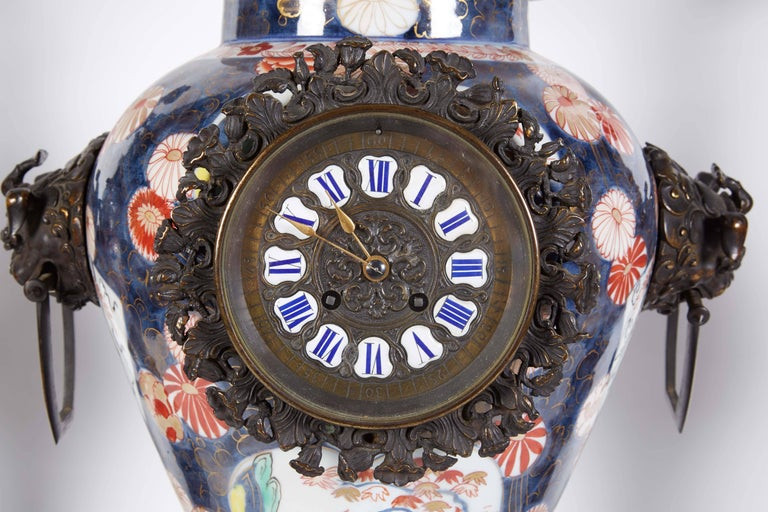 A French Japonisme parcel-gilt patinated bronze and Japanese Imari Porcelain clock garniture, circa 1880. In the manner of Edouard Lievre.  Mounted with bronze dragons and elephant heads, very finely made.  The clockworks stamped H. Sequin,