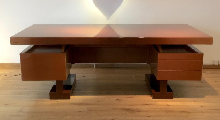 An extremely handsome desk designed by Pierre Cardin. The strong geometric volumes are enhanced by the luxurious caramel lacquer finish. A single deep drawer on the left, three shallow drawers on the right (the top one fitted for pens, etc).