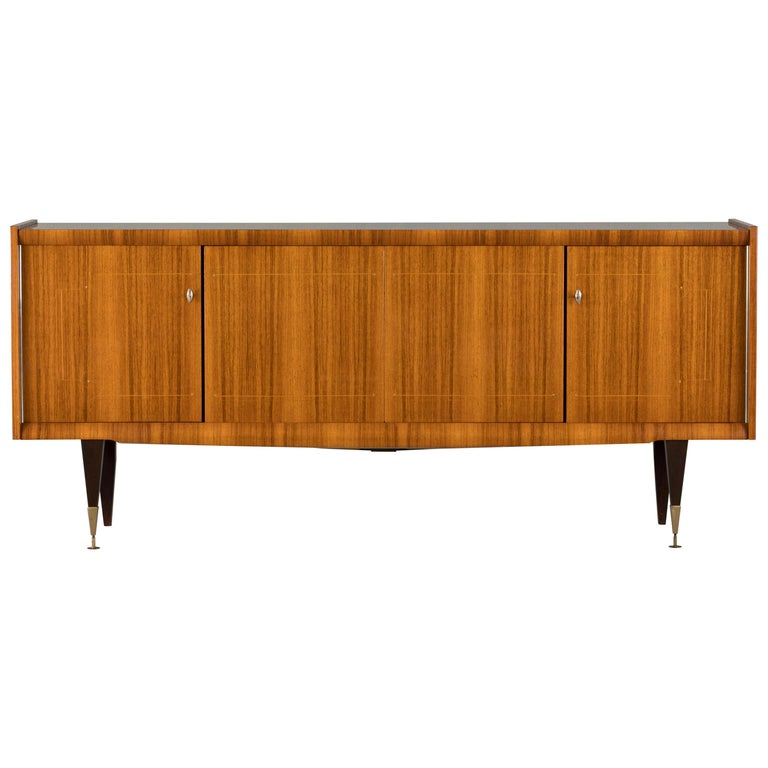 French Art Deco sideboard, credenza, with bar cabinet. The sideboard features stunning Macassar ebony wood grain with a thin decorative mother of pearl inlaid design. It offers ample storage, with shelve behind two doors on the left and a dovetailed