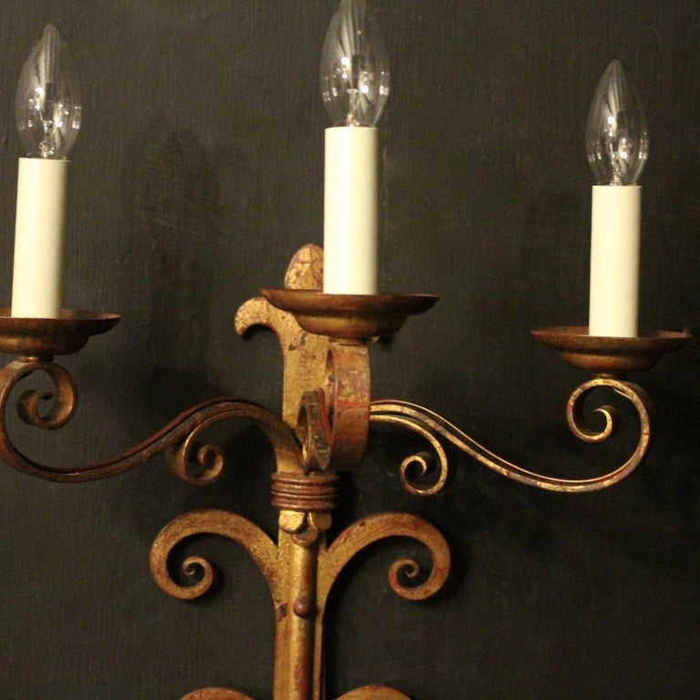A large decorative pair of French gilded wrought iron triple arm antique wall lights, the rectangular gauge scrolling arms with circular bobeche drip pans, issuing from an elongated twin scrolled backplate with fleur de lys finial and terminal, nice