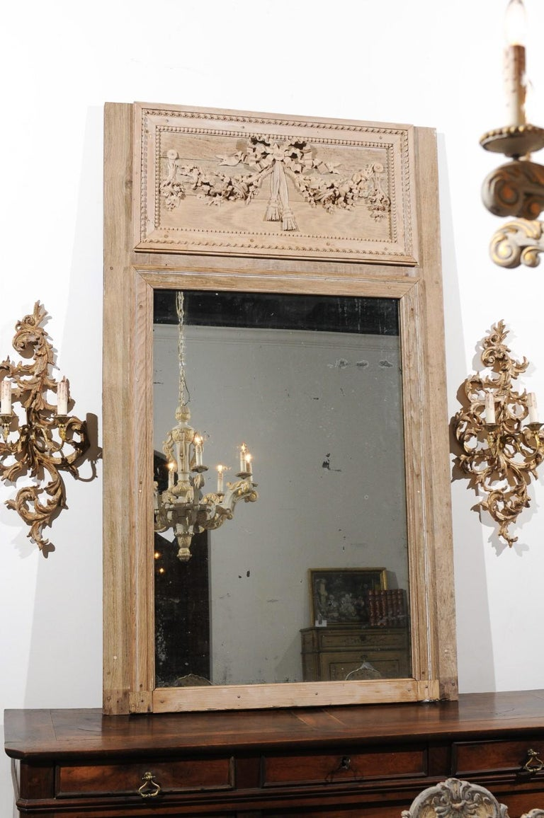 A French Louis XVI period carved wooden trumeau mirror from the late 18th century, with ribbon-tied garland of flowers and twisted motifs. Born in the later years of the 18th century, this exquisite wooden trumeau mirror features in its upper